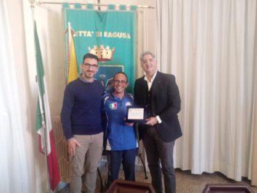 Luca Poli, componente della squadra azzurra di pesca con canna da riva riceve una targa ricordo dal Comune